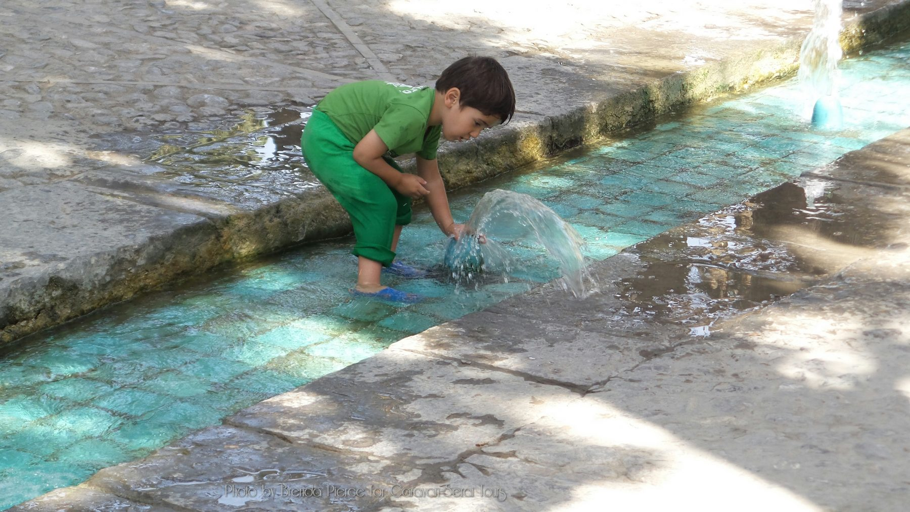Children playing in the fountains at Fin Garden in Kashan