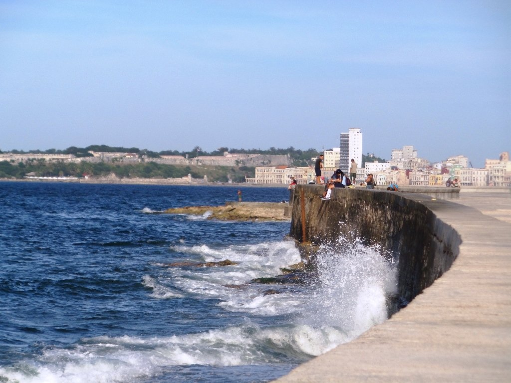 People enjoying the breeze off the ocean on the Malecon